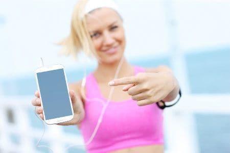 kobieta w stroju biegowym pokazuje smartphona