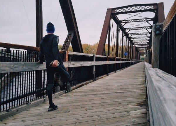 biegacz miejski rozciąga się na moście